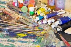 工作场所画家,在手中掠过,有树胶水彩画颜料的,帆布瓶子为 免版税库存图片