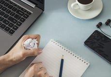 工作场所 有一杯笔记本和铅笔膝上型计算机智能手机耳机咖啡的女性手 库存图片