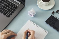 工作场所 有一杯笔记本和铅笔膝上型计算机智能手机耳机咖啡的女性手 图库摄影