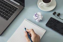 工作场所 有一杯笔记本和铅笔膝上型计算机智能手机耳机咖啡的女性手 免版税库存图片