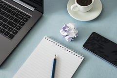 工作场所 有笔记本和铅笔膝上型计算机智能手机耳机的女性手 图库摄影