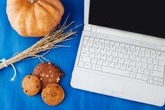 工作场所 膝上型计算机、笔记本、笔、曲奇饼和橙色切片在一张木桌上 笔在焦点 免版税库存照片