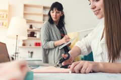 工作处理在两名裁缝妇女缝合的演播室  缝合小企业 衣物设计师队缝合并且创造 图库摄影