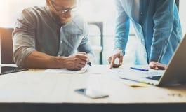 工作处理照片的两个工友 工作与同事一起的少妇在现代办公室顶楼 配合概念 免版税库存图片