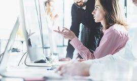 工作处理现代办公室的工友 照片谈论项目负责人的队新的事务 年轻创造性的乘员组工作 免版税库存照片