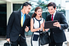 工作外面在片剂个人计算机的亚裔买卖人 免版税库存照片
