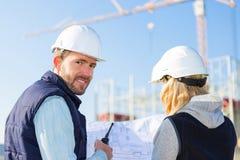 工作外面在建造场所的两名工作者 免版税图库摄影