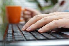 工作夜间在办公室和饮用的咖啡的膝上型计算机 免版税库存图片