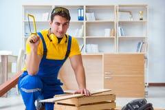 工作安装工的木匠锯一个木板用手sa 免版税图库摄影