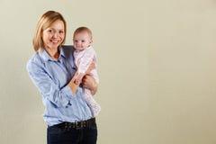 工作室被射击愉快的母亲和婴孩 免版税库存照片