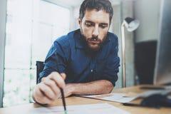 工作当代笔记本的年轻英俊的商人,当坐在木桌上在晴朗的办公室时 人藏品 图库摄影