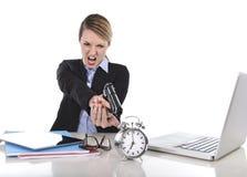 工作愤怒的恼怒的女实业家指向枪闹钟在时间概念外面 免版税库存照片