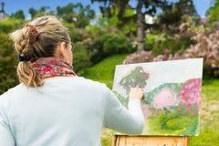 工作户外在公园或雀鳝的后面观点的一位女性艺术家 图库摄影