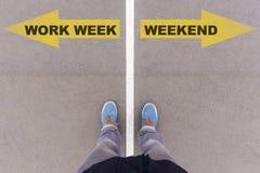 工作星期对周末在沥青地面、脚和sho的文本箭头 免版税图库摄影
