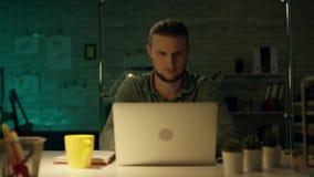 工作晚小时的年轻人可胜任的建筑工程师在他的办公室 办公室是黑暗的仅他的桌光打开 股票录像