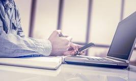 工作普通设计膝上型计算机的商人 触摸屏智能手机 全世界连接技术接口 库存图片