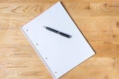 工作有笔记本和圆珠笔的书桌在木桌上 免版税库存照片