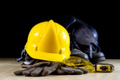 工作服、盔甲、手套和玻璃在一个木工作表上 免版税库存照片