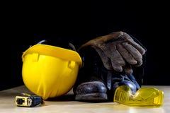 工作服、盔甲、手套和玻璃在一个木工作表上 库存图片