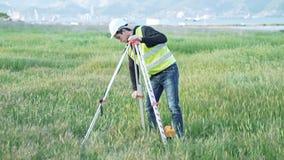 工作服的一位男性测量员调整在建造场所的设备 风景设计,测量学的概念 影视素材