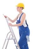 工作服的少妇电工与在梯子的螺丝刀我 免版税库存照片