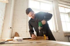 工作服的年轻熟练的木匠使用钻子,木匠业木制品 库存照片