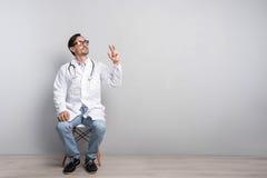 工作服的愉快的医生坐椅子 图库摄影