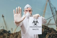 工作服的技术员在关于有害废料的垃圾填埋警告 免版税图库摄影