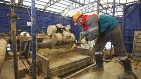 工作服的民工倾斜与刀片的岩石在探险的挖泥机机器 股票视频
