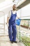 工作服装的建筑工人,防护手套拿着一件盔甲和一把锤子 在高处的工作 在b的脚手架 免版税库存照片