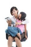 工作母亲和女儿有片剂的 库存图片