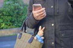 工作母亲,当儿童` s玩具黏附在她的提包外面 免版税库存照片