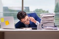 工作狂商人劳累了过度与许多工作在办公室 图库摄影