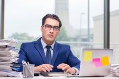 工作狂商人劳累了过度与许多工作在办公室 免版税库存图片