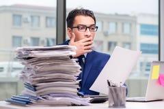 工作狂商人劳累了过度与许多工作在办公室 免版税库存照片