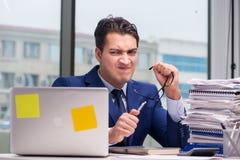工作狂商人劳累了过度与许多工作在办公室 免版税图库摄影
