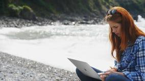 工作狂妇女坐在海海滩并且工作甚而在旅行休息 影视素材