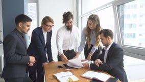 工作环境在办公室 查验文件的雇员在工作场所 组商人讨论 库存照片