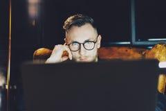 工作现代顶楼办公室的照片年轻经理 坐在葡萄酒椅子的人在晚上 使用当代膝上型计算机 图库摄影