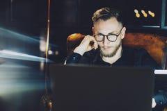 工作现代顶楼办公室的年轻经理 坐在葡萄酒椅子的人在晚上 使用当代膝上型计算机,被弄脏 免版税图库摄影