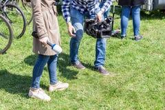 工作电视的记者户外 写报告的Journalsit和摄影师在街道在明亮的晴天 免版税库存照片