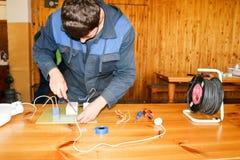 工作的人工作电工,收集大白色街灯,在工业的一个中转的电路有导线的 免版税库存图片