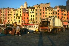 工作的人收集垃圾在俯视Portovenere的色的大厦口岸的码头的黎明 库存图片