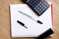 ?? 工作的办公室在办公室 i 笔、铅笔、统治者、计算器和一个干净的笔记本 白色名单 免版税库存照片