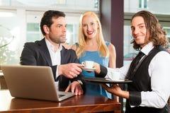 工作的同事-坐在咖啡馆 免版税库存照片