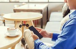 工作的商人用途手机在咖啡馆 免版税库存照片
