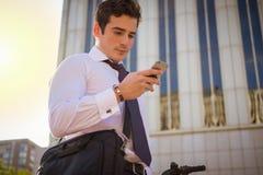 工作的年轻商人骑马在城市 免版税库存照片