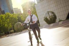 工作的年轻商人骑马在城市 库存图片