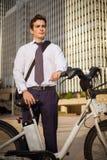 工作的年轻商人骑马在城市 库存照片