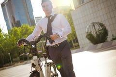 工作的年轻buinessman骑马在城市 库存照片